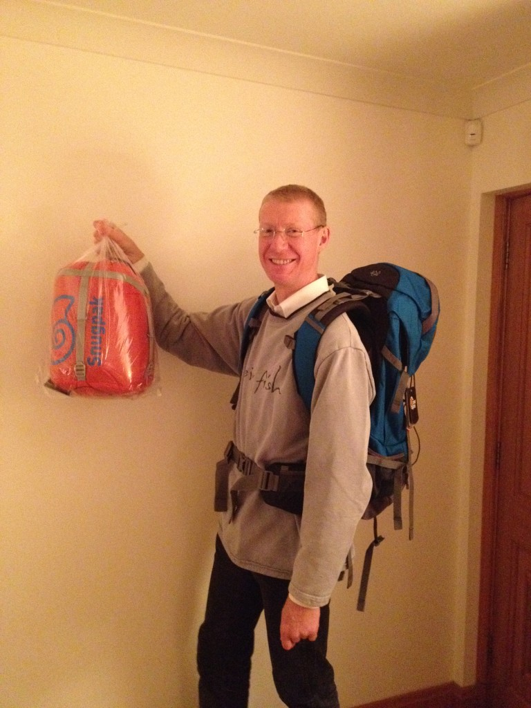 Picture of AD wearing rucksack and holding sleeping bag